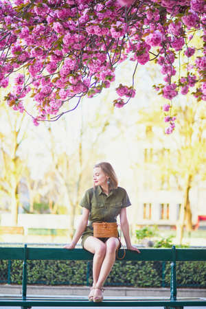 Belle femme française marchant à Paris un jour de printemps à la saison des cerisiers en fleur