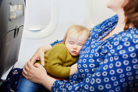 Woman with little girl travelling by plane. Mother holding her sleeping baby during the flight. Travelling with kids Stock Photo