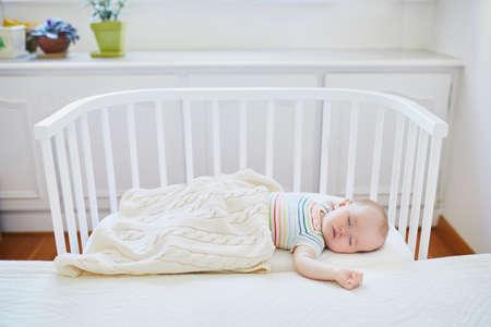 Urocza dziewczynka śpi w łóżeczku sypialnym przymocowanym do łóżka rodziców. Małe dziecko o drzemkę w łóżeczku. Koncepcja treningu snu. Niemowlę dziecko w słonecznym przedszkolu