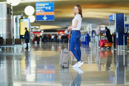 Jonge vrouw op de internationale luchthaven die met bagage loopt, klaar voor haar vlucht