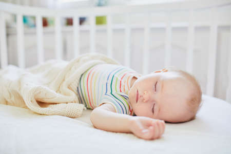 Adorable baby girl sleeping in co-sleeper crib attached to parents bed. Little child having a day nap in cot. Sleep training concept. Infant kid in sunny nursery Stock Photo
