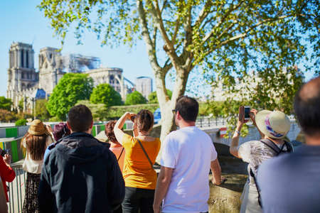 People taking photos of Notre Dame cathedral without roof and spire destroyed by fire in Paris, France Stock fotó