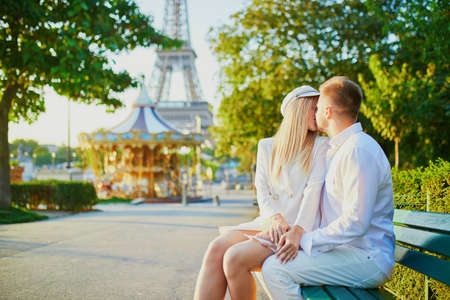 Romantic couple having a date near the Eiffel tower. Tourists in Paris enjoying the city Banco de Imagens - 122079068