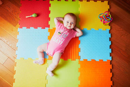 4 months old baby girl lying on colorful play mat on the floor in bodysuit with words 'It's my daddy's first father's day'. Activity carpet for kids
