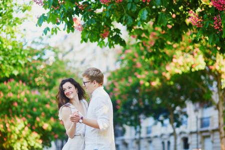 Happy romantic couple in Paris, hugging under pink chestnuts in full bloom. Tourists spending their vacation in France