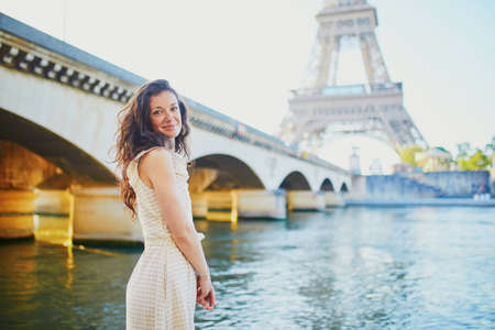 Happy young girl in Paris, near the Eiffel tower. Tourist spending their vacation in France