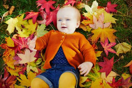Schattig klein meisje in heldere, stijlvolle kleding die op het gras ligt en speelt met kleurrijke herfstbladeren op een herfstdag in het park Stockfoto