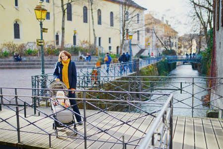 Happy young woman with her little baby girl in stroller. Mother walking with daughter in alpine town of Annecy, France