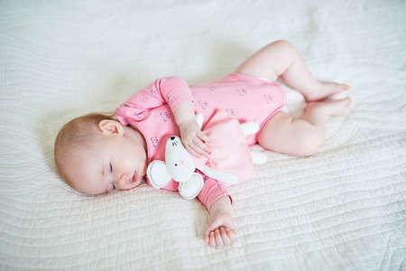 Niña tomando una siesta con su juguete favorito de ratón. Niño durmiendo en la cama con edredón. Concepto de entrenamiento del sueño. Niño infantil en vivero soleado