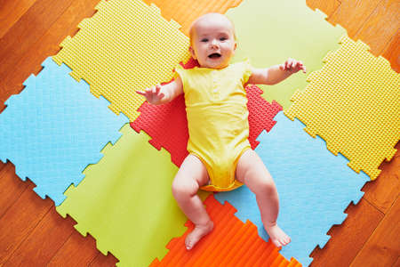 Happy smiling baby girl lying on colorful play mat on the floor, view from above