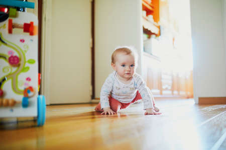 Baby girl learning to crawl. Happy healthy little child on the floor. Infant kid at home Banque d'images - 124577084
