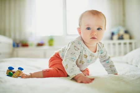 Baby girl sitting on bed. Happy healthy little child at home. Infant kid in sunny nursery Banque d'images - 124575923