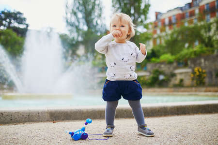 Adorable little girl outdoors in park eating bread. Toddler playing with a toy on a street of Paris. Outdoor activities for kids