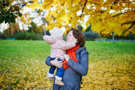 Happy young mother with her adorable daughter walking together on a fall day. Woman and baby girl outdoors in park. Autumn activities with kids