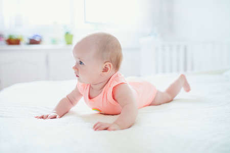 Cute baby girl lying on her tummy. Happy healthy kid at home in nursery