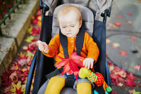 Adorable little girl in bright stylish clothes sitting in pushchair outdoors on a fall day. Autumn walks with kids Banque d'images - 124575749