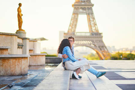 Happy romantic couple in Paris, near the Eiffel tower at sunrise. Tourists spending their vacation in France