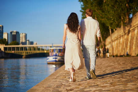 Happy romantic couple in Paris, near the river Seine. Tourists spending their vacation in France