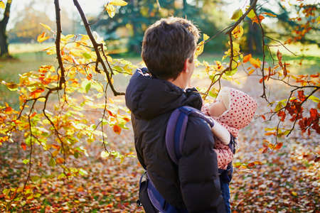 Young father with his daughter in carrier walking together on a fall day. Man and baby girl outdoors in park. Autumn activities with kids