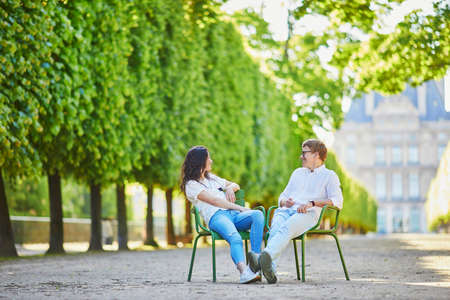 Happy romantic couple in Paris, sitting on traditional green metal chairs in Tuileries garden. Tourists spending their vacation in France 스톡 콘텐츠