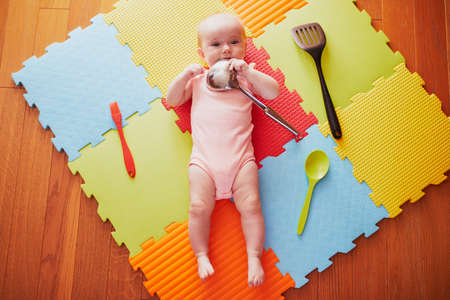 Baby girl with kitchen utensils. Little child lying playmat and playing with kitchenware. Real things as toys for children. Infant kid in sunny nursery.