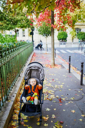Adorable little girl in bright stylish clothes sitting in pushchair outdoors on a fall day in Paris, France. Autumn walks with kids