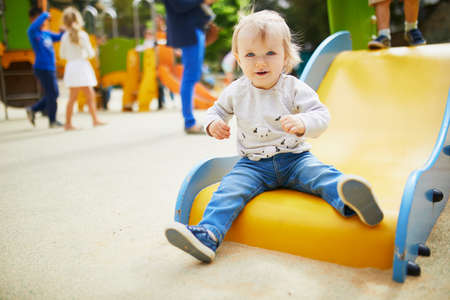 Adorable little girl on playground on a sunny day. Toddler looking playing on a street. Outdoor activities for kids
