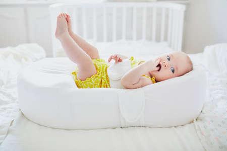Cute dziewczynka leżąc w kokonie. Szczęśliwe zdrowe dziecko w przedszkolu