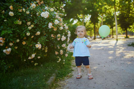 Adorable little girl with green balloon outdoors in park on a sunny day. Toddler looking at flowers. Kid exploring nature 스톡 콘텐츠