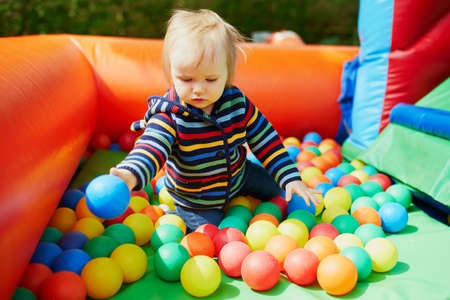 Little girl playing in ball pool. Toddler having fun with balls. Colorful toys for children. Banque d'images - 124575628