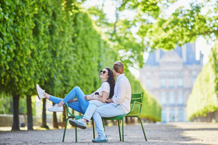 Happy romantic couple in Paris, sitting on traditional green metal chairs in Tuileries garden. Tourists spending their vacation in France