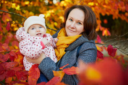 Happy smiling woman with baby girl on sunny fall day in park. Beautiful family of two in bright red foliage. Autumn activities with kids Stock Photo - 124575492