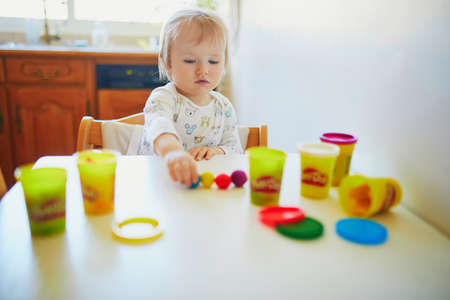Adorable little girl playing with modelling clay at home. Toddler using playdough for making sculpture. Creative activities for kids Stock Photo