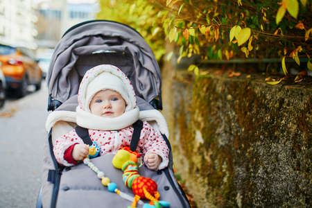 Happy little child, baby girl in stroller with colorful autumn leaves outdoors on a sunny fall day. Outdoors seasonal activities for kids