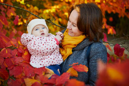 Happy smiling woman with baby girl on sunny fall day in park. Beautiful family of two in bright red foliage. Autumn activities with kids