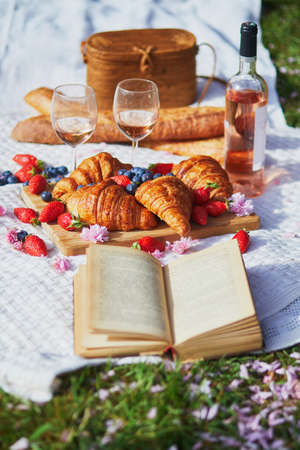 Beautiful picnic with rose wine, French croissants and fresh berries served for two on the grass covered with pink fallen petals and flowers