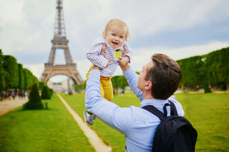 Father holding his adorable daughter in Paris near the Eiffel tower. Family on vacation in France. Travelling with kids