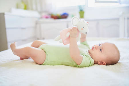 Cute baby girl lying on her back on bed with soft toy. Happy healthy kid at home in nursery