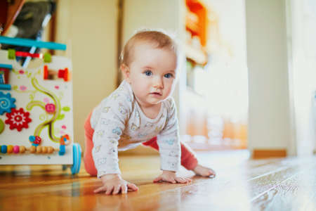 Baby girl learning to crawl. Happy healthy little child on the floor. Infant kid at home Foto de archivo - 124574404