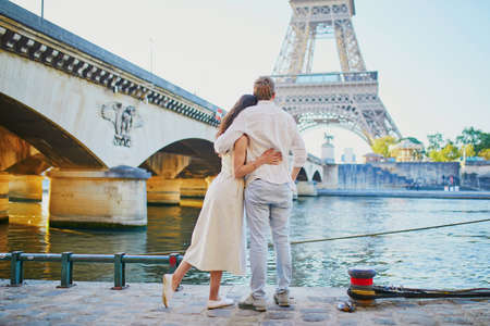 Happy romantic couple in Paris, near the Eiffel tower. Tourists spending their vacation in France