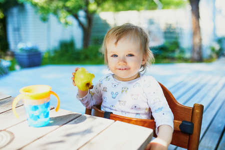 Cute baby girl eating apple at the outdoor table on a warm summer day. Little kid tasting solids at home. Baby led weaning