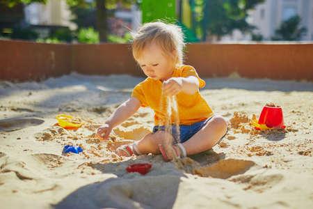 Adorable niña en el patio de recreo en el arenero. Niño jugando con moldes de arena y haciendo mudpies. Actividades creativas al aire libre para niños Foto de archivo