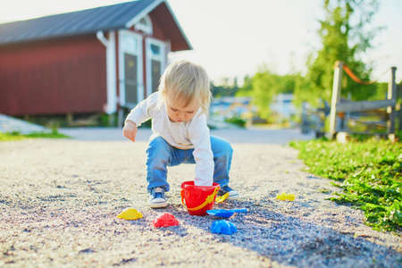 Toddler playing with sand molds, bucket and shovel, making mudpies and gathering small stones. Outdoor creative activities for kids 写真素材 - 126768893