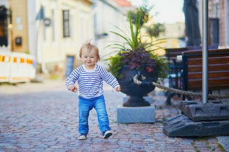 Happy smiling toddler walking in the street of Finnish town Porvoo, Finland Reklamní fotografie
