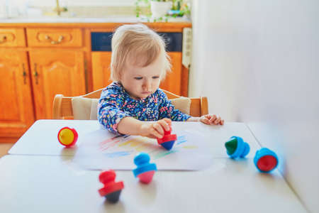 Adorable little girl drawing with wax pencils at home, in kindergaten or preschool. Creative games for kids Stock Photo