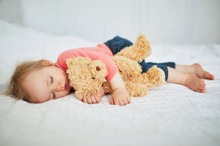 Adorable baby girl sleeping with her favorite toy. Little child having a day nap and hugging a teddy bear. Infant kid resting in nursery