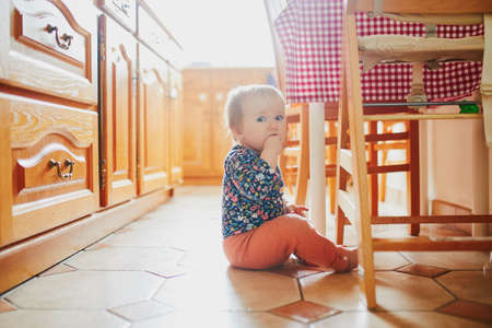 Baby girl sitting on the floor in the kitchen. Little child at home Archivio Fotografico