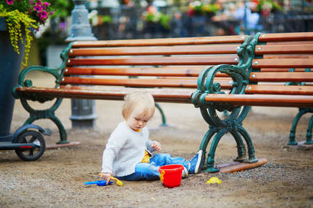 Little baby girl sitting on the ground near bench on a street of Helsinki, Finland. Toddler playing with sand molds, bucket and shovel, making mudpies and gathering small stones. Outdoor creative activities for kids 写真素材 - 126768915
