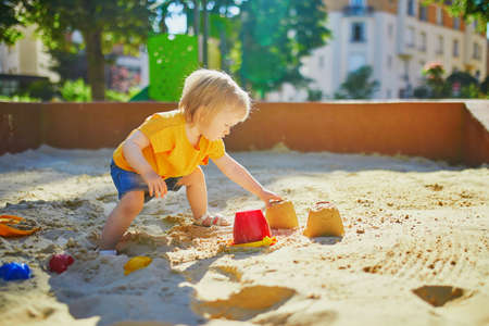Adorabile bambina sul campo da giuoco in recinto di sabbia. Bambino che gioca con gli stampi di sabbia e fa i mudpies. Attività creative all'aperto per bambini