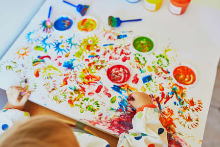 Hand of little girls painting with fingers at home, in kindergaten or preschool. Creative games for kids
